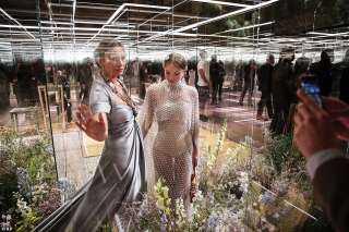 عارضة أزياء وابنتها تشاركان في عرض أزياء في باريس.. العارضات بعيدات عن الجمهور  داخل أقفاص زجاجية
